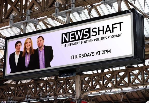 "an advertising board shows a banner of two men and a women with tagline ""NewsShaft"""